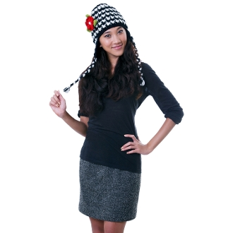 black and white earflap hat with a red flower and fleece lining and tassels